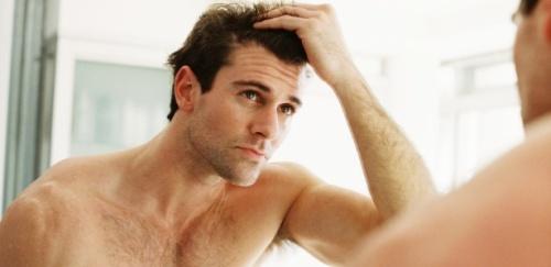 homem-se-olhando-no-espelho-comeco-de-calvicie-checando-calvicie-perda-de-cabelo-1371074378366_615x300